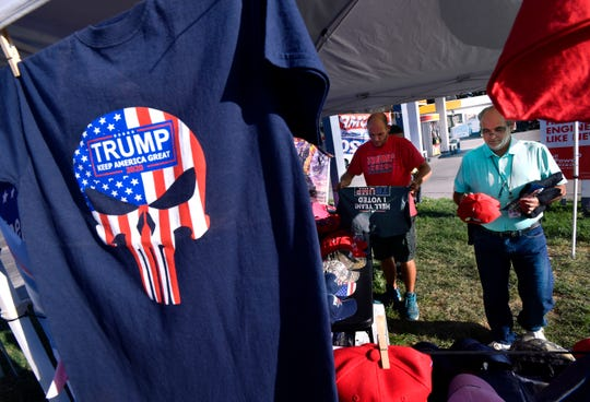 Brian Ayotte examines a red Donald Trump cap after trying on a Trump shirt Friday. There are three Trump Shop tents in Abilene until Tuesday, including this one at South First and Leggett streets. The other two are at the intersection of Barrow and South 27th streets and at 4424 Buffalo Gap Road.