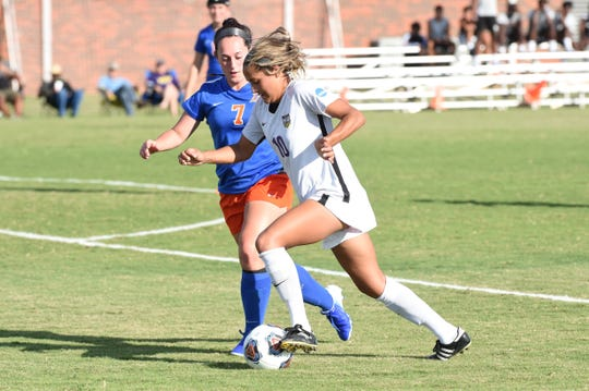 HSU's Randie Dennison (10) passes a Louisiana College defender at the HSU Soccer Complex on Thursday, Sept. 26, 2019. The Cowgirls won 10-0.