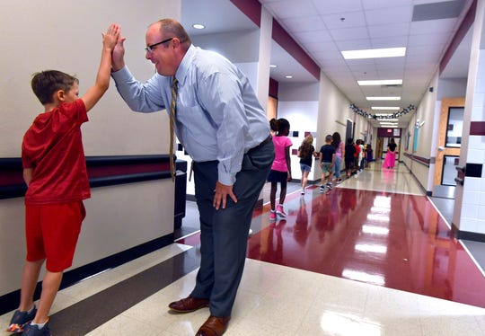 Clay Johnson, assistant principal at Bowie Elementary School, high-fives a student in a hallway as students walk single-file back to their room on the first day of classes this year, Aug. 21. It was Johnson's first day after making a transition from his role as Cooper High School band director.