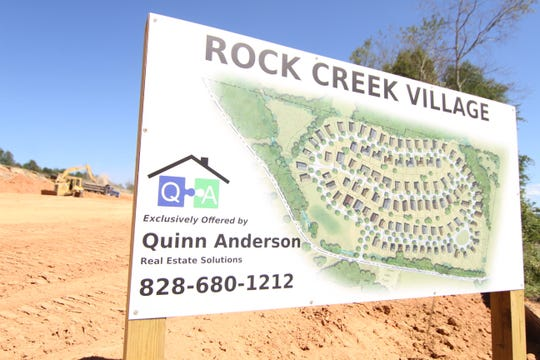 A sign along Parkway View Drive in Mars Hill offers a rendering of the Rock Creek Village development.