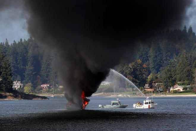 Firefighters aboard the Bremerton Fire Department boat douse a fully involved boat fire outside of the Bremerton Yacht Club in Phinney Bay on Friday.