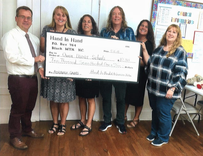 Counselors from each school in the Owen School District accept a check from Hand in Hand of the Swannanoa Valley on Sept. 16.