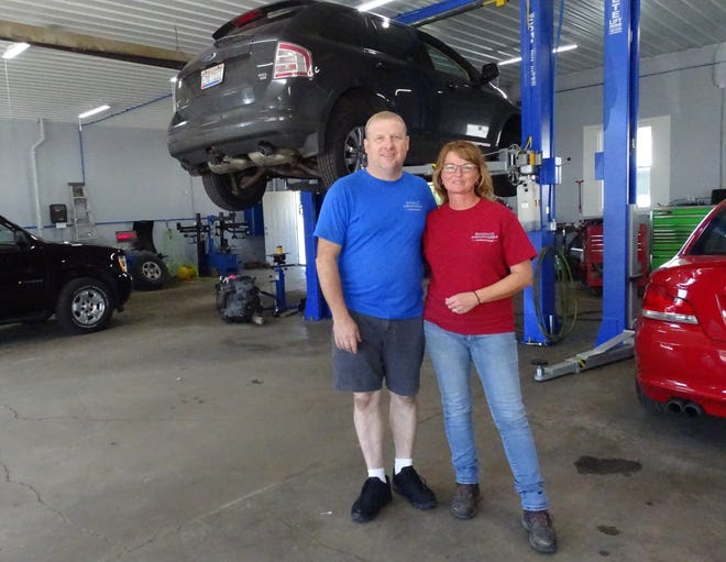 Matt and Mindy Hensley stand in the garage of their new business, M&M Auto Repair, 301 W. Mary St.