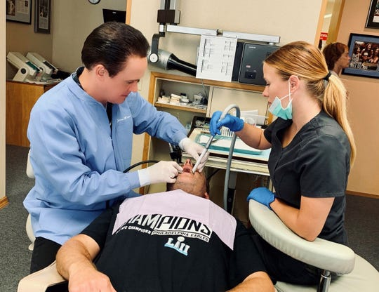 Dr. James M Wiener working with a patient.