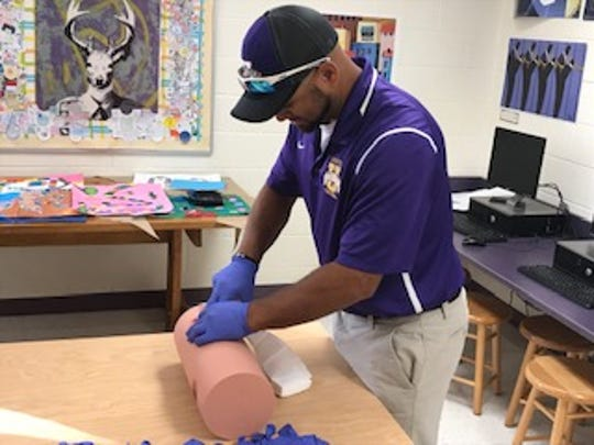 Brian Netter, assistant coach for the Unioto High School football team, stuffs a simulated wound during a Stop The Bleed training event Friday.