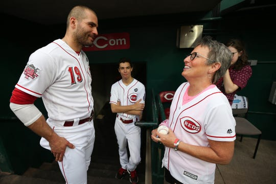 Cancer survivor Laura Fay, who served as the team's honorary bat girl, receives an autograph from Cincinnati Reds first baseman Joey Votto (19) before the first inning of an MLB baseball game against the Chicago Cubs, Thursday, May 16, 2019, at Great American Ball Park in Cincinnati.
