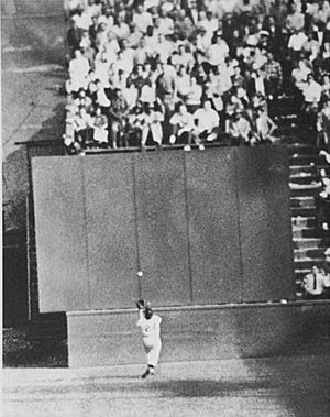 Running at top speed with his back to the plate, New York Giant center fielder Willie Mays gets under a 450-foot blast off the bat of Cleveland first baseman Vic Wertz to pull the ball down in front of the bleachers wall in the eighth inning of the World Series opener at the Polo Grounds in New York on September 29, 1954. In making the miraculous catch with two runners on base, Willie came within a step of crashing into the wall.