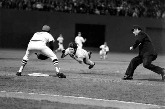Pete Rose of the Cincinnati Reds is shown diving into third base in the ninth inning of Game 7 of the World Series at Fenway Park in Boston, Ma., on Oct. 23, 1975.  Rose advances from first on Joe Morgan's single.  The third baseman of the Boston Red Sox is Rico Petrocelli.