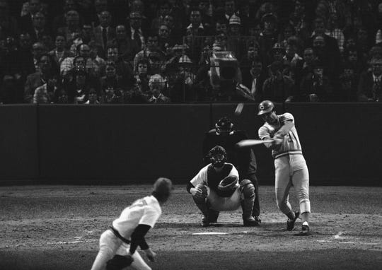 Tony Perez slams a homer over the left field screen in sixth inning, scoring Johnny Bench ahead of him, to cut Bostons lead to 3-2 in last World Series game, Oct. 22, 1975, Boston, Mass. Boston catcher is Carlton Fish and umpire is Art Frantz.