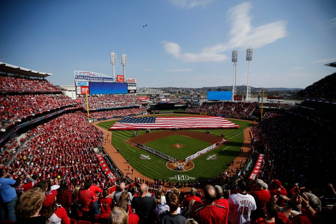 Fans rise for the National Anthem as two F-16 fighter jets fly over the stadium before the Opening Day game between the Cincinnati Reds and the Pittsburgh Pirates at Great American Ball Park in downtown Cincinnati on Thursday, March 28, 2019.