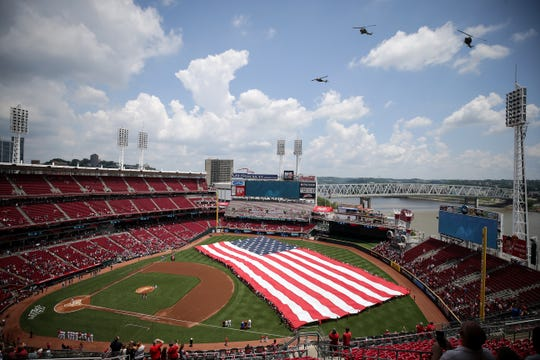 Three UH-1 Huey helicopters fly over as a giant American flag is unfurled before the first inning of an MLB baseball game between the Milwaukee Brewers and the Cincinnati Reds, Thursday, July 4, 2019, at Great American Ball Park in Cincinnati..