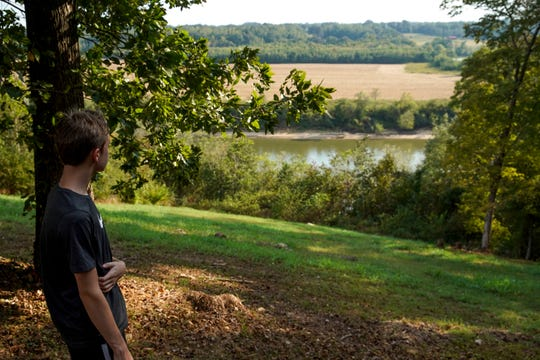 """Mason Brennan, 13, looks over his backyard where an unconscious man was found near the cliffs overlooking the Cumberland at Queens Bluff Neighborhood in Clarksville, Tenn., on Friday, Sept. 27, 2019. Brennan noticed a man in the morning that same day when leaving for school. """"If he was homeless you would think he would want to sleep in the shade,"""" Brennan said, motioning to the right side of their yard. """"He must have fell down the hill, with how exposed he was in the sun."""""""