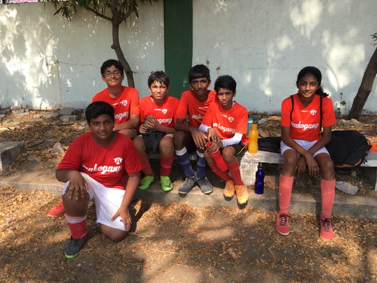 Janani Shivakumar, right, with boys soccer players in India.