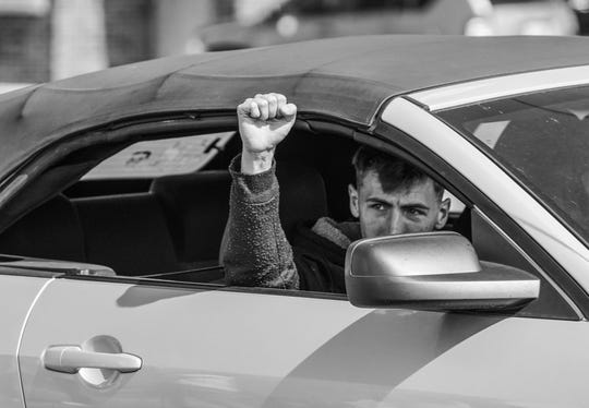 A man throws a fist up in solidarity for UAW members on strike against General Motors outside of Flint Assembly as he drives along Van Slyke Rd. in Flint on Tuesday, September 24, 2019. Ford workers say ratification is not a certainty.