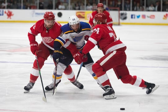 Detroit Red Wings forward Dominic Turgeon, left, and defenseman Madison Bowey, reach for the puck with St. Louis Blues forward Nathan Walker, Sept. 26, 2019, at the Calumet Colosseum, in Calumet, Mich.