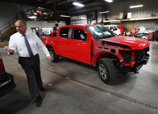 Matthews Hargreaves Chevrolet general manager Walt Tutak walks through the body shop, where concerns of part deficiencies due to the strike, could keep cars from getting repaired at the dealership in Royal Oak, Michigan on September 27, 2019.