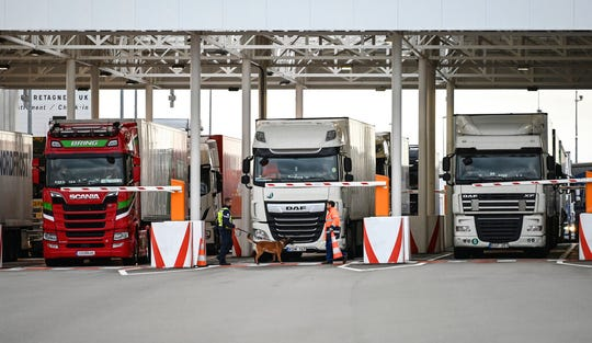 In this Tuesday, Sept. 17, 2019 file photo, an employee of Eurotunnel and his dog check trucks on their way to Britain during a day of test in case of no deal Brexit, at the exit of the Channel tunnel in Calais, northern France.