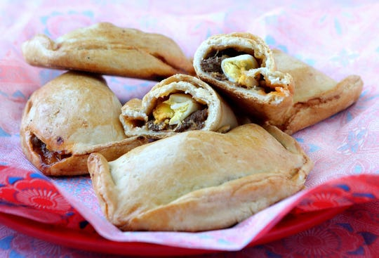 Baked meat empanadas with egg and olive.