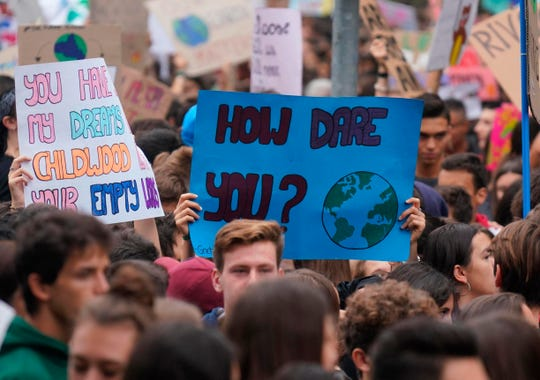 Students hold up posters with excerpts of teenage activist Greta Thunberg's message at the United Nations as they demonstrate during a worldwide protest demanding action on climate change, in Milan, northern Italy, Friday, Sept. 27, 2019.