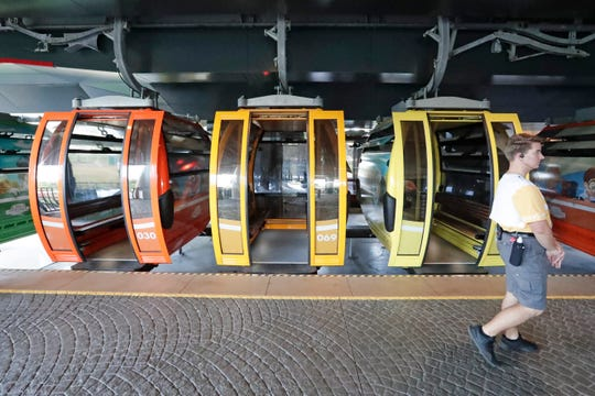 A Disney cast member walks by gondolas as they move from a station to various locations at Walt Disney World.