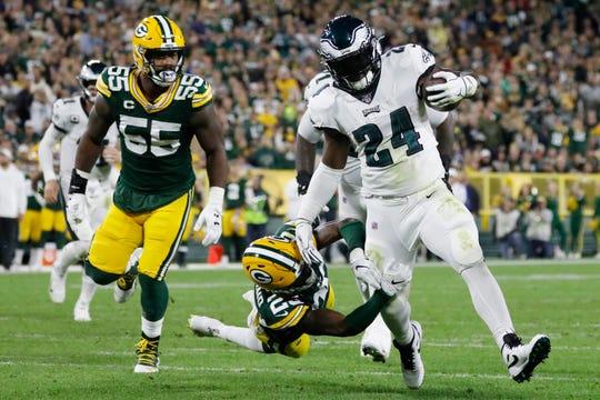 Philadelphia Eagles running back Jordan Howard breaks the tackle of Green Bay Packers cornerback Jaire Alexander during the first half on Thursday.