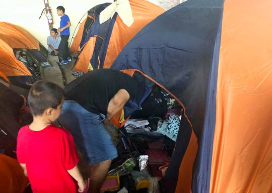 Julio Lopez, a Salvadoran man who wants to seek asylum in the United States with his family, speaks with his wife inside their tent at a migrant shelter in Tijuana with his 5-year-old son by his side in Tijuana, Mexico, Thursday, Sept. 26, 2019. He asked that their faces not be shown.