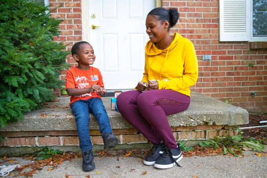 "Tay Harris, talks with her son, Joshua Moore, 4, on the porch of their home in Terre Haute, Ind., Thursday, Sept. 26, 2019. ""It has to be pitch dark outside for me to turn a light on,"" said Harris, 25. She said she wants to help with climate change and considers it common sense to save electricity. ""If you have the beautiful sun that God blessed us with, use it."""