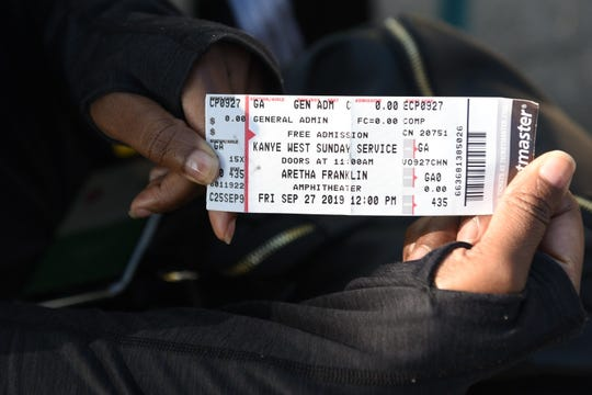 Tiffany Walker of St Clair Shores shows off the concert ticket  outside the Aretha Franklin Amphitheatre for Kanye West Sunday Service concert on Friday, September 27, 2019.