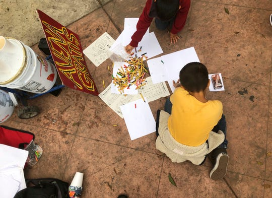 A Mexican boy draws with crayons while his family waits in Tijuana, Mexico, for their names to be called from a waiting list to claim asylum at a border crossing in San Diego Thursday, Sept. 26, 2019. An advocacy group served free oatmeal at left.