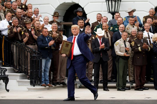 President Donald Trump holds a plaque of appreciation from America's Sheriffs and Angel Families as he walks from a ceremony on the South Lawn the White House in Washington, Thursday, Sept. 26, 2019.