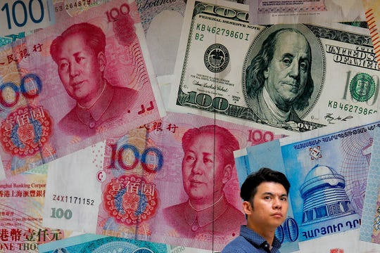 In this Aug. 6, 2019, file photo, a man walks past a money exchange shop decorated with different banknotes at Central, a business district in Hong Kong. The Trump administration is discussing ways to limit U.S. portfolio flows into China, which would affect billions of dollars in investment.