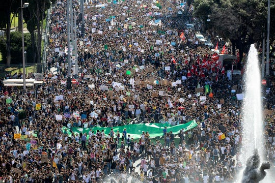 "Students demonstrate during a worldwide protest demanding action on climate change, in Rome, Friday, Sept. 27, 2019. Writing on banner reads in Italian' ""Change the system, not the climate."""
