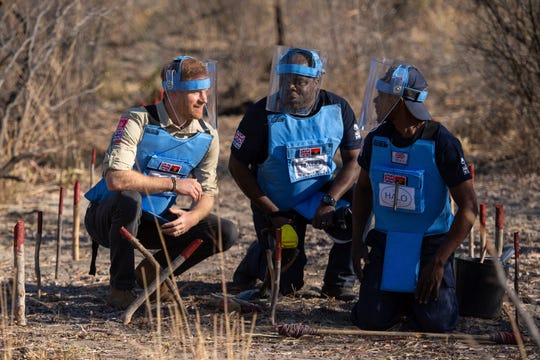 Britain's Prince Harry with Jose Antonio, center, of the Halo Trust and a mine clearance worker walk through a minefield in Dirico, Angola Friday Sept. 27, 2019, during a visit to see the work of landmine clearance charity the Halo Trust.