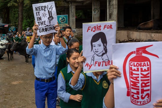 Exile Tibetan school children carry posters during an awareness march in Dharmsala, India, Friday, Sept. 27, 2019.
