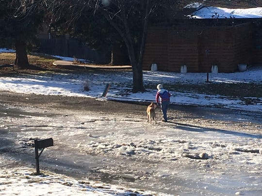 A Country Club Estates resident walks on an ice flow on Hillside Drive.