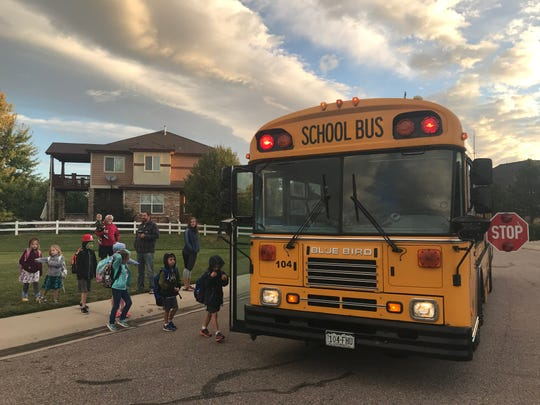 Elementary students in the Highland Meadows neighborhood board a Podure School District school bus Friday morning.
