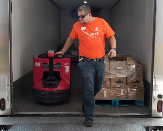 Mike Davis of the Harry Chapin Food Bank moves pallets of food donations from the Lee County School District on Friday, September 27, 2019, in Fort Myers.