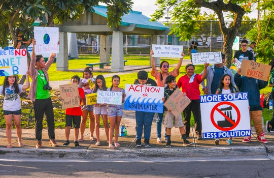 Micronesia Climate Change Alliance members and other supporters gather during a wave at the ITC Intersection in this Sept. 27 file photo as part of the Global Climate Strike.