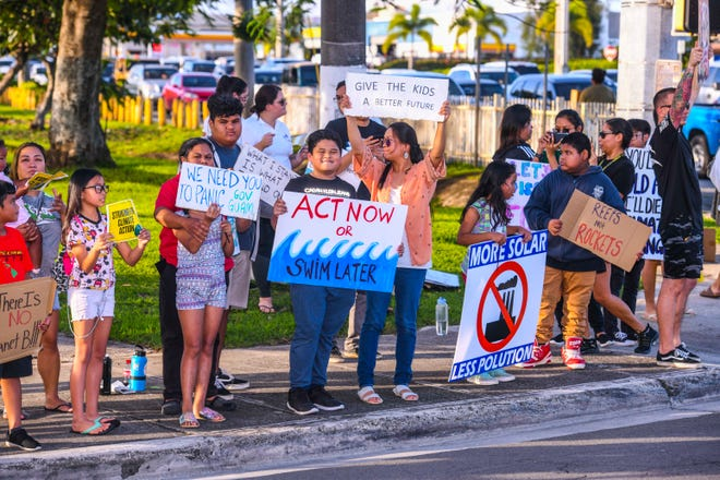 Micronesia Climate Change Alliance members and other supporters gather during a wave at the ITC Intersection in this Sept. 27 file photo.
