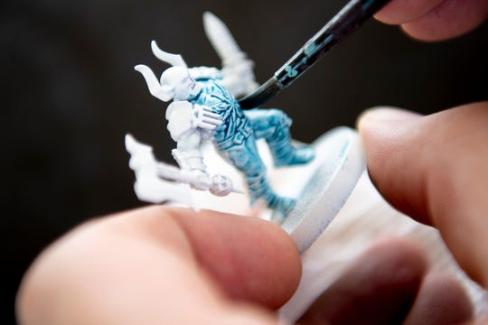 The Dented Mug co-owner Dallas Fitzgerald paints a Warhammer miniature figurine in Knoxville, Tennessee on Thursday, September 26, 2019.