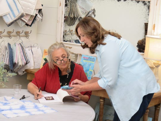 Annie Sloan signs a copy of her latest book for a customer at Back Porch Mercantile.