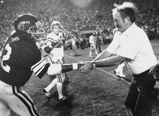 LSU coach Charles McClendon congratulates a USC player after the No. 20 Tigers lost, 17-12, to the No. 1 Trojans in Tiger Stadium on Sept. 29, 1979, after leading 12-3 in the fourth quarter.