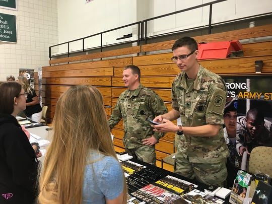 U.S. Army Staff Sgt. Alex Parke (left) and Sgt. Kyle Hannum talk to visitors Friday at the Ohio Means Jobs/Fairfield County Job and Family Services job fair at Ohio University Lancaster.