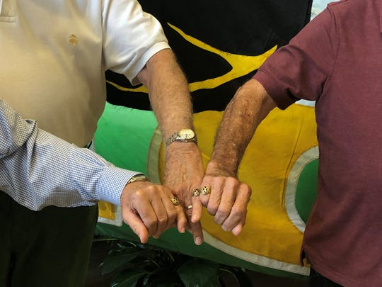 Bob Kirchner (right), a 1955 graduate of St. Xavier high school, shows his class ring with two friends. The 82-year-old was reunited with his rings after more than 60 years when a Louisville man found it on the property at Swiss Hall.