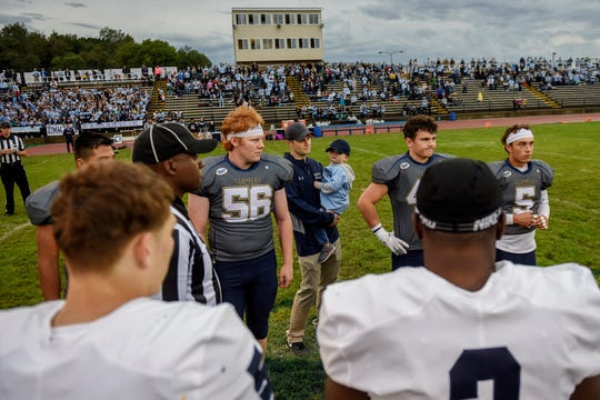 DeWitt assistant coach Marcus Fray, center, holds his son Weston as they join Panthers and Trojans players for the coin toss before the start of the game on Friday, Sept. 27, 2019, in DeWitt.