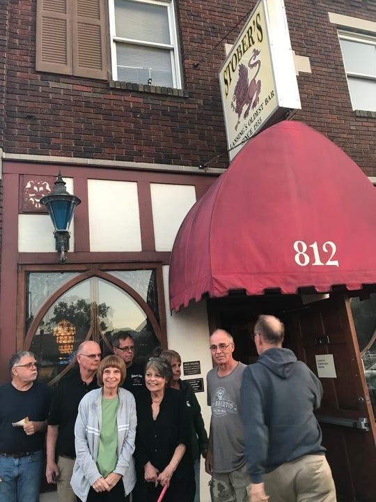 Larry Schneider, right, organizes a family photo at Stober's bar Sept. 23, 2019. From Left, Bill Schneider, Dan Schneider, Gretchen Mikula, Mike Schneider, Kristine Thatcher, Kathi Mailand and Andrew Schneider, all grandchildren of Katie Schneider.