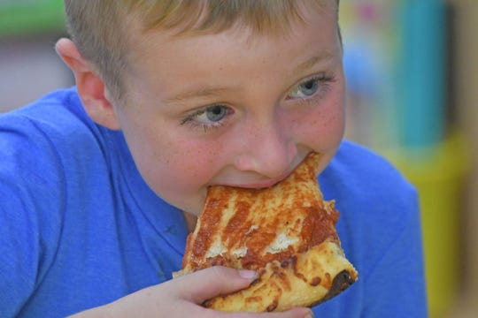 Patrick Smith enjoys his pizza Thursday afternoon at Western Elementary.