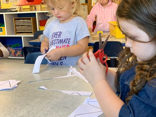 Using safety scissors, preschoolers Melanee and Gracie cut out shapes during an activity session at the Pine Street KinderCare Center in Waukesha. Activities such as this are part of the center's emphasis on learning.