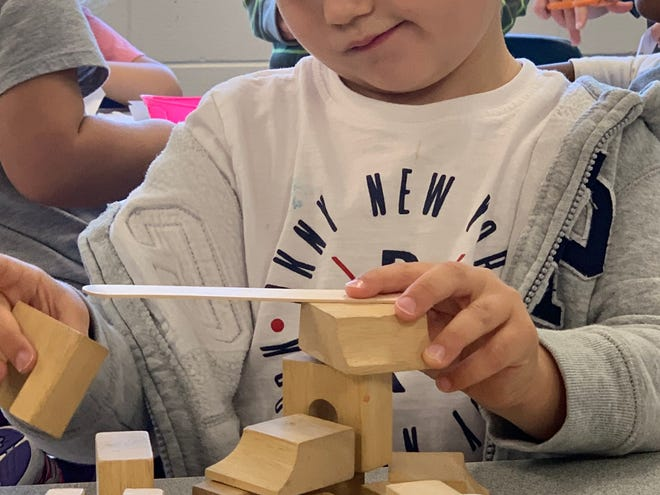 Rory, a preschooler at KInder Care's Pine Street center in Waukesha, ponders what to add to this building-block structure.
