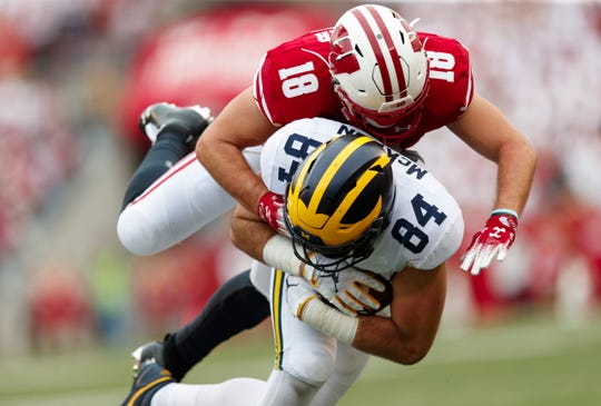Sep 21, 2019; Madison, WI, USA; Wisconsin Badgers safety Collin Wilder (18) tackles Michigan Wolverines tight end Sean McKeon (84) during the third quarter at Camp Randall Stadium. Mandatory Credit: Jeff Hanisch-USA TODAY Sports